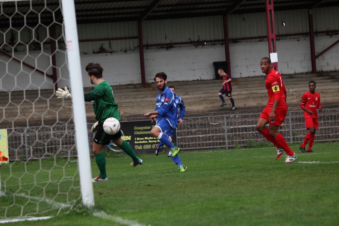 Sam Conlon scores for Hythe past Jack Eden of Carshalton